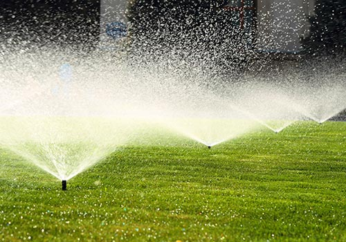 four lawn sprinklers shooting water